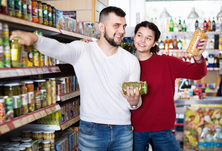 Glad  pleasant smiling couple standing near shelves with canned goods at store