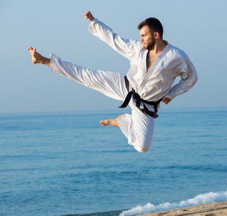 Active young man doing karate at ocean quay in dawn Stock Photo