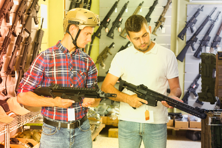 Portrait of two positive friends choosing air-powered gun in army market
