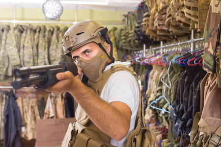 european adult guy in military equipment with weapon in army shop