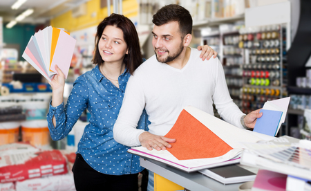Beautiful young couple examining color scheme variants in paint supplies supermarket Stock Photo