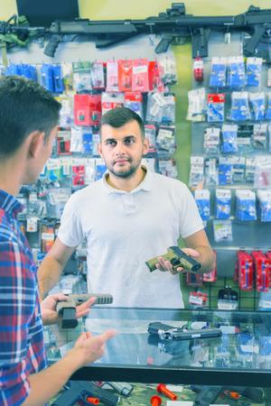 positive british guy haelping customer to choose handgun in army market Stock Photo