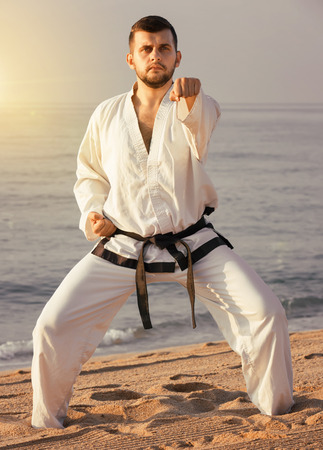 Young  guy demonstrates karate poses at seaside in sunset outdoor