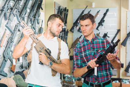 Portrait of two positive male friends choosing air-powered gun in army market