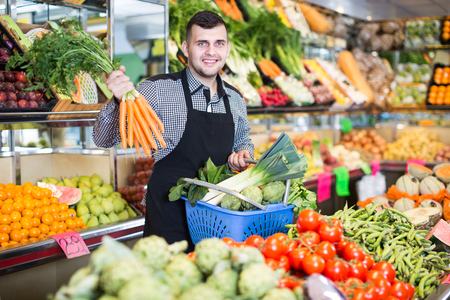 Young man seller helping to buy fruit and vegetables in grocery shop 스톡 콘텐츠