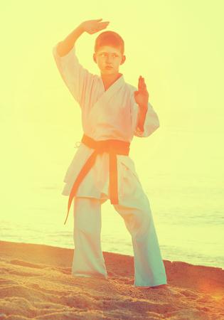 Boy doing karate poses at  sunset sea shore
