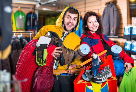 Smiling tourists show purchased things for hikes in a sports equipment store