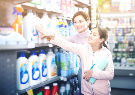 Positive woman with daughter choosing best cleaners in supermarket Stock Photo