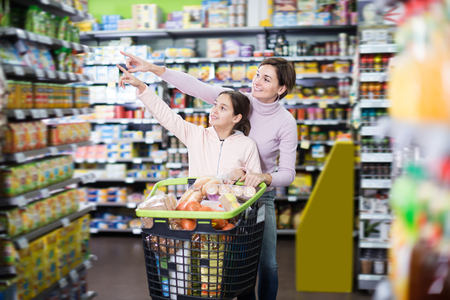 sorts: Positive woman with daughter shopping with shopping cart in supermarket