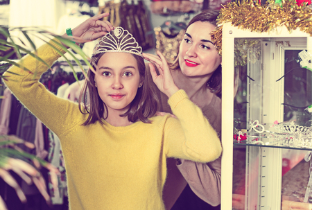 Happy cheerful positive mother and daughter choosing festive accessories in children's cloths shop Stock Photo