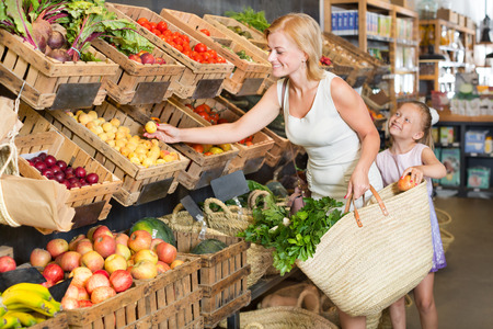 Glad young mother with daughter shopping a various fruits in food store
