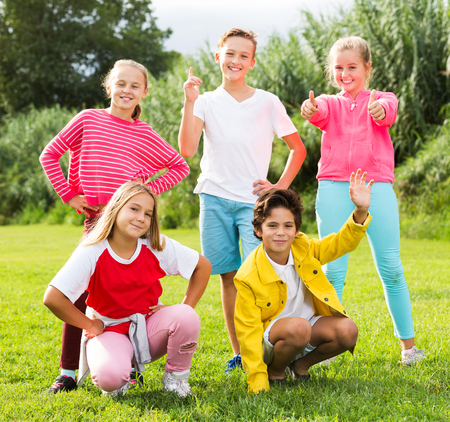 Portrait of five smiling children who are walking and posing in the park
