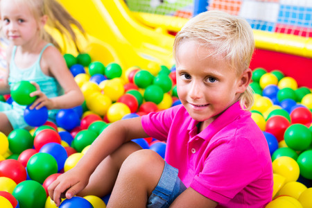 Small european boy in elementary school age sitting and playing with multicolored plastic balls Stock Photo