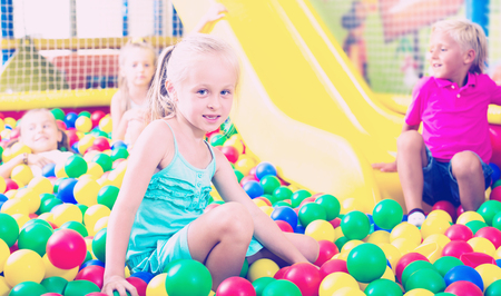 Smiling small girl in elementary school age playing with multicolored plastic balls Stock Photo
