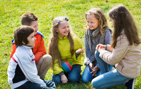 Group of happy  children laughing and chatting in spring park Stock Photo