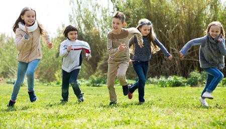 Vrolijke kinderen vol energie rennen door het veld Stockfoto