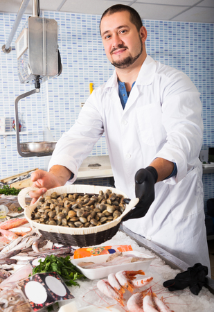 Positive man in uniform behind fish counter holds small basket of mussels