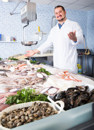 mature man with beard arms folded standing near fish counter