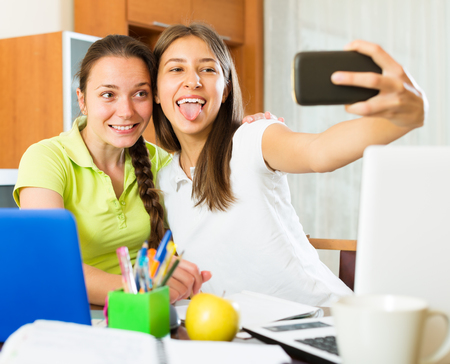 Student girls sitting at the table and making photo on mobile phone at home Imagens