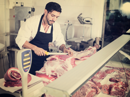 Handsome butcher is cutting meat for clients in market