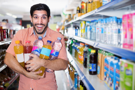 Positive man is posing with drinks near shelves in hypermarket