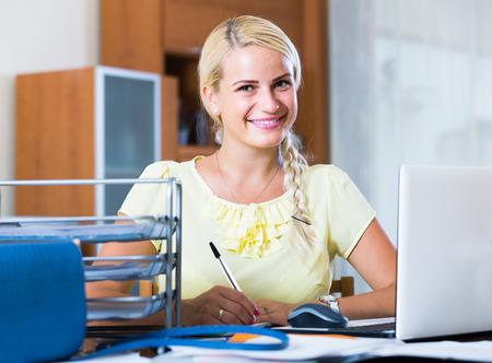 Portrait of happy european female secretary working in office
