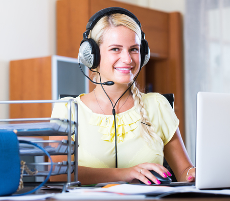 house call: Happy  young blonde woman with headset working at laptop