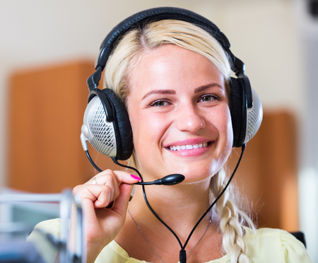 Cheerful young woman with headset working at laptop  inside Stock Photo