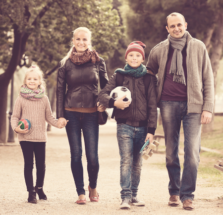 Joyful family with two children spending weekend together outdoors