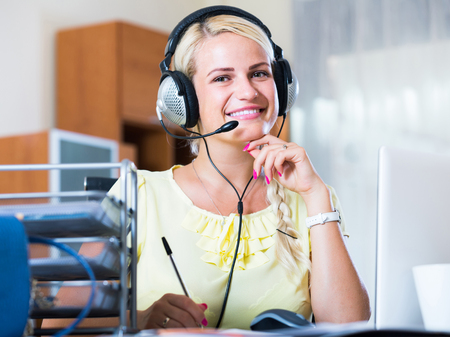 young russian girl answering the call of technical support and smiling Stock Photo
