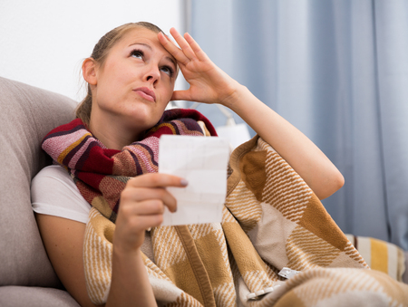 Sick woman lying at home on cozy sofa with plaid and reading recipe Stock Photo