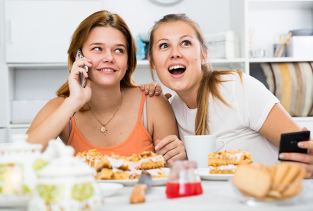 Girl is overhears what her girlfriend is talking to her boyfriend by phone at home. Stock Photo