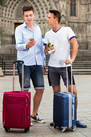 Happy cheerful  male couple  with luggage using the map at smartphone