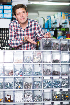 Young employee selling nuts, screw and fasteners in hardware store Stock Photo
