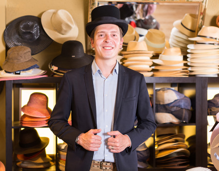 cheerful english adult male shopping in botique and try on cylinder hat