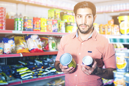 Adult  cheerful positive male is choosing conserved peas in market. Stock Photo