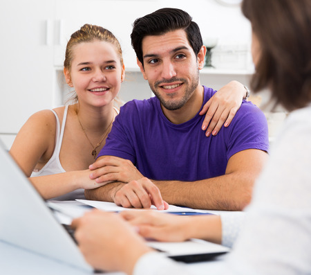 kin: Young smiling couple consulting with female real estate agent in home interior