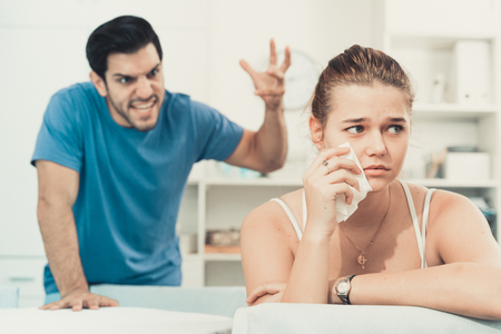 Frustrated girl sitting at home table on background with angry boyfriend
