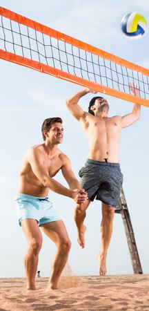 Zwei smilling Mann spielen im Volleyball in der Zeit, die nahe Ozean stillsteht.