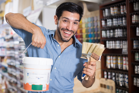 Smiling man choosing brushes and varnishes for home renovation in paint store