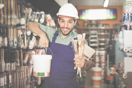 boasting: Cheerful master satisfied with purchases in paint store standing with picked paint and tools