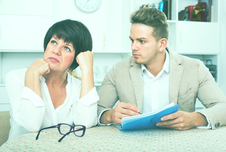 Ordinary woman has discontentedly turned away from man who suggests her to sign documents Stock Photo