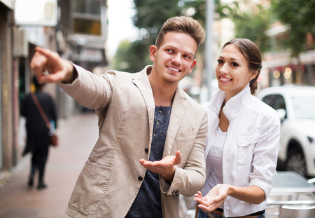 Young positive woman showing direction to guy at the street