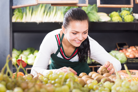 Smiling woman seller putting kiwis on display in a grocery shop Stock Photo