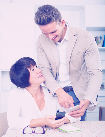 specifies: Son telling his mature mother how to use phone Stock Photo
