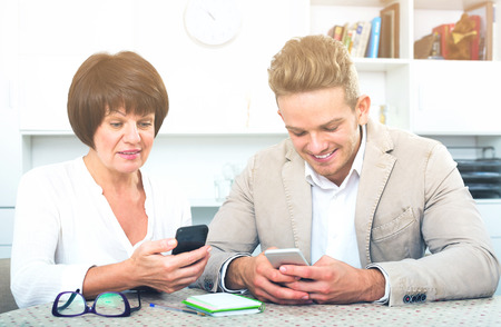 specifies: Happy mature mother with her handsome son studing new functions of smartphones