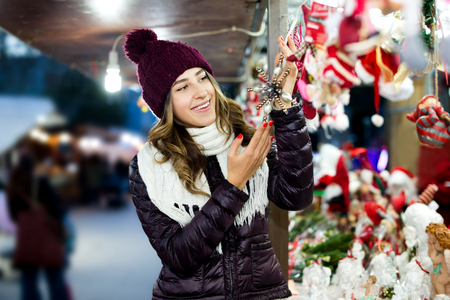overspending: Positive young girl choosing Christmas decoration at market in evening time