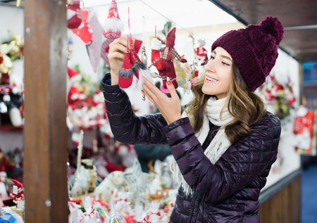 overspending: Smiling teen girl buying christmas gifts at market