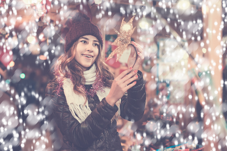 overspending: Smiling girl staying at market with small Christmas trees