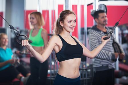 Aktives glückliches lächelndes Gewichtheben der Leute im modernen Fitnessstudio Standard-Bild - 88691618